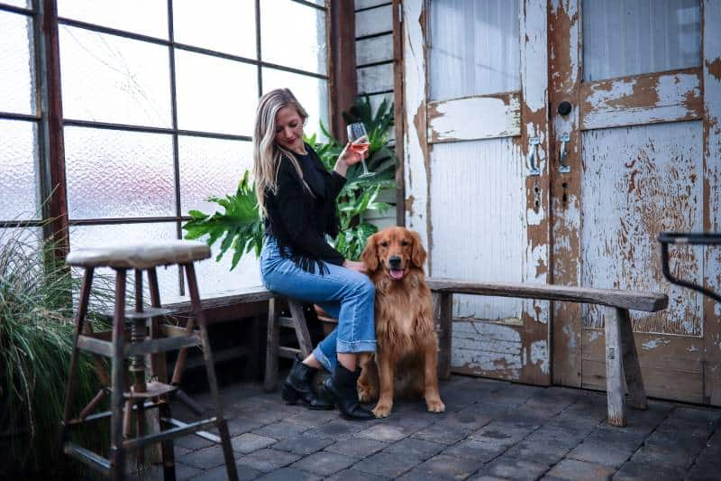 woman sitting on chair beside dog while holding glass of drink