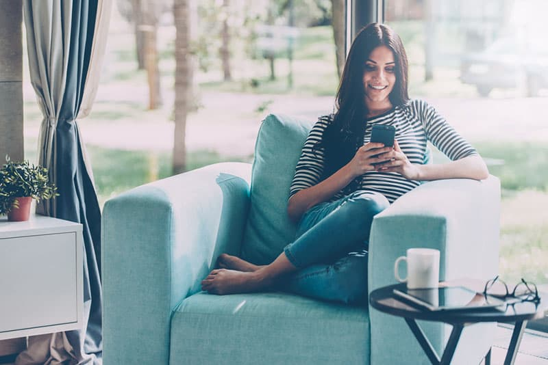 woman sitting on sofa and texting