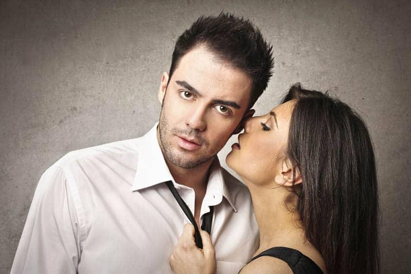 woman whispering on mans ear