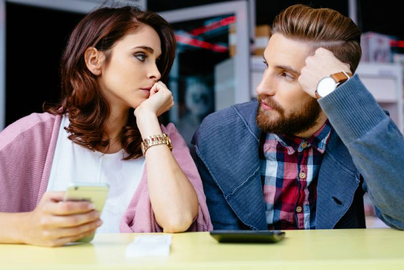 worried couple looking at each other at cafe