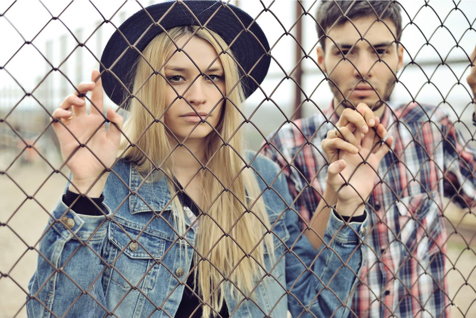 young couple outdoors with serious faces standing behind lattice fence