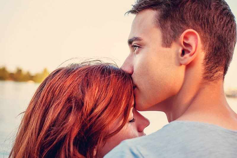 young woman kissing a woman in forehead