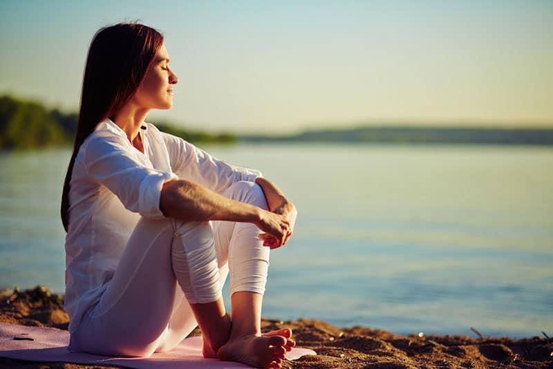 young woman meditates on the beach
