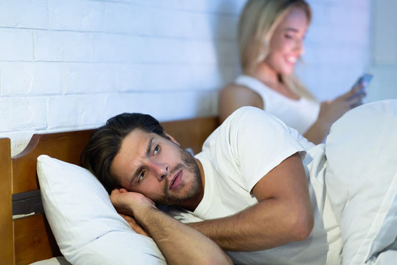 jealous man laying next to woman in bed