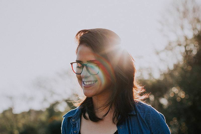 portrait of smiling woman with eyeglasses outdoors