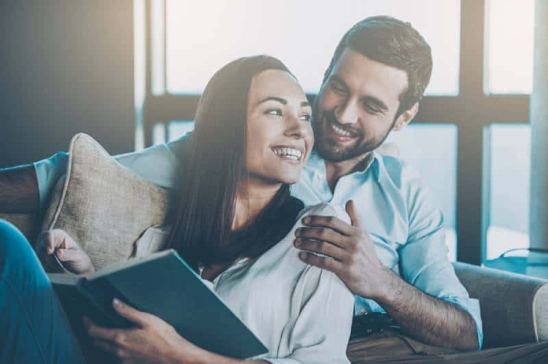 Beautiful young loving couple bonding to each other and smiling while woman holding a book