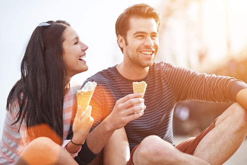 Couple laughs and eats ice cream