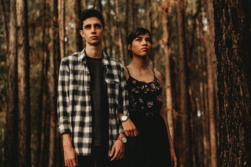 young couple standing outside surrounded by trees