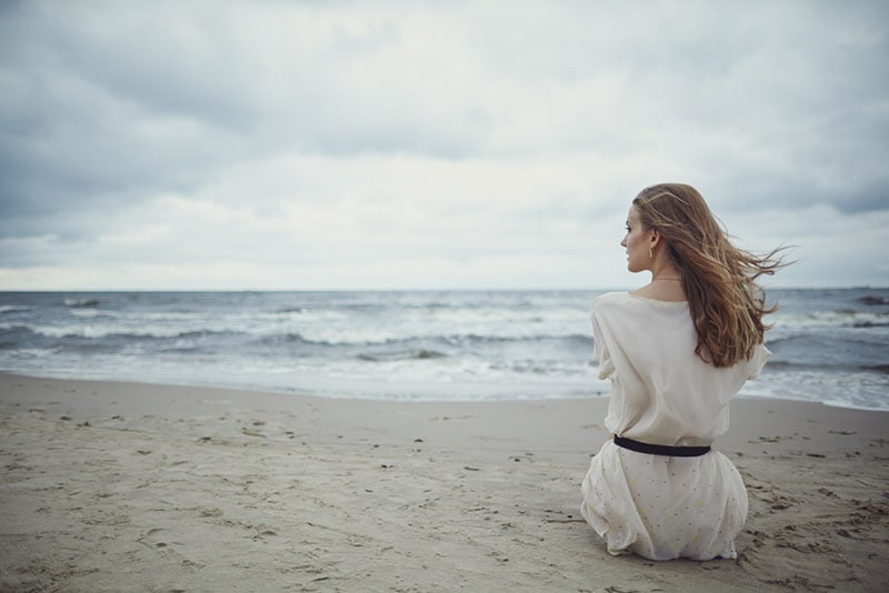 lonely woman sitting on the beach
