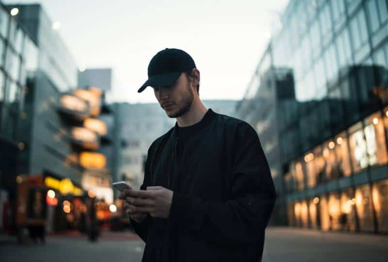 Man in black jacket with black cap talking on the phone