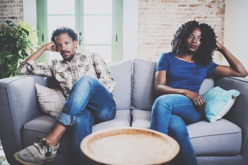 Men argue with his girlfriend, who is sitting next to him on the couch