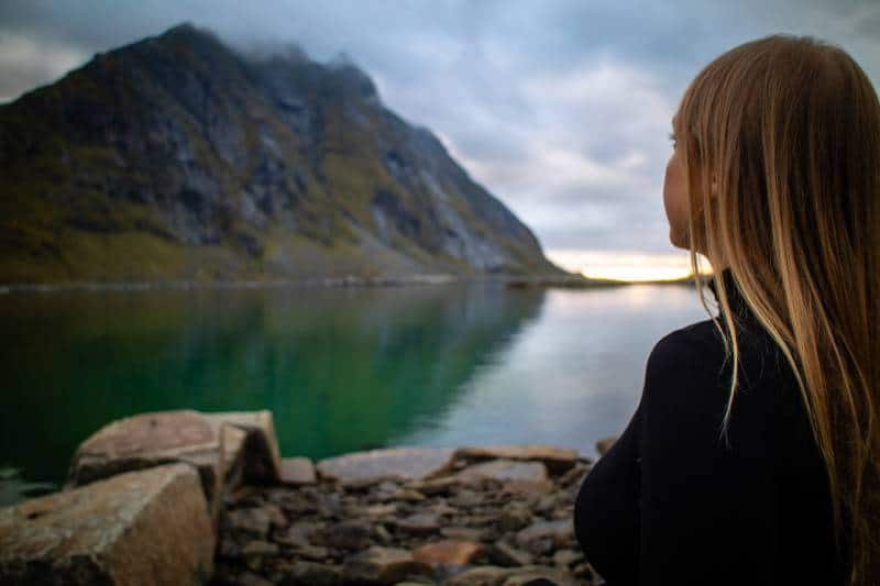 Woman in black jacket sits on rocks near lake during the day