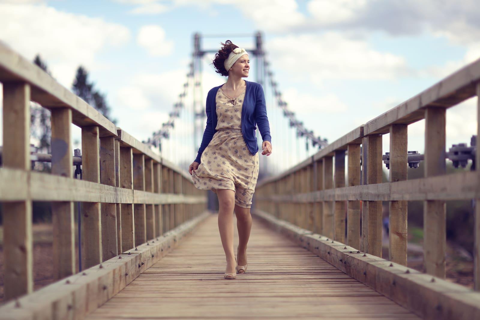 a woman walks across the bridge