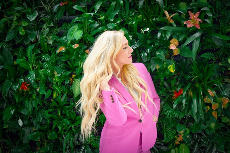 blond woman in pink suit posing
