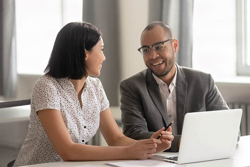 business male and female talking at office desk