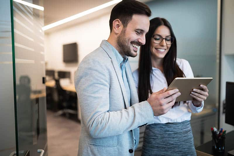 business man and woman looking at tablet