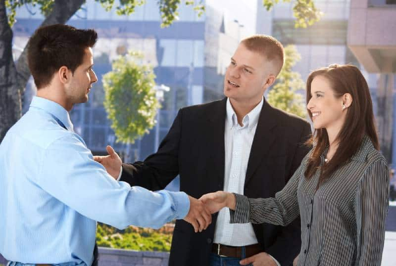 business people meeting outside, man introducing woman to his colleague