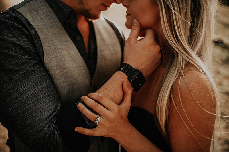 closeup photo of man touches woman face