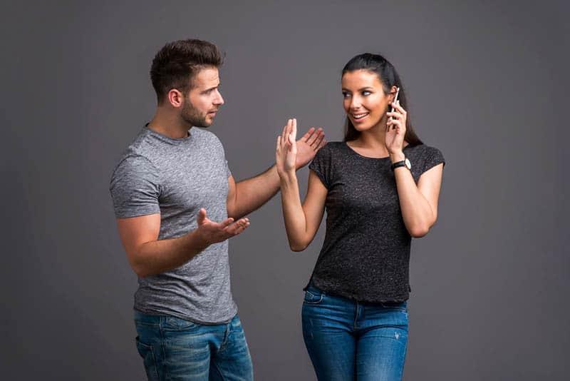 confused man looking at woman speaking on phone