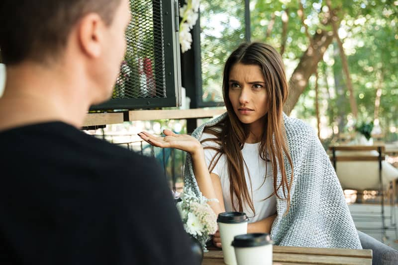 confused woman looking at man in street cafe