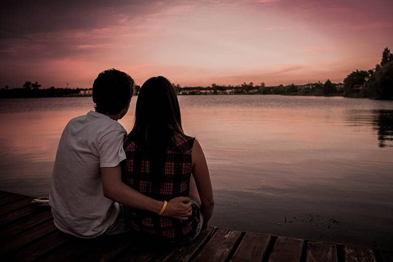 couple hugs on wooden dock in front of water
