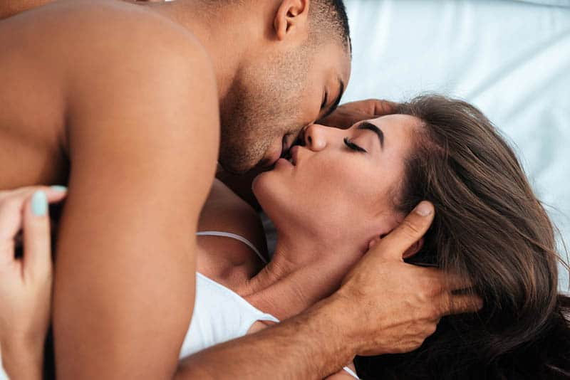 couple kissing with closed eyes in bedroom