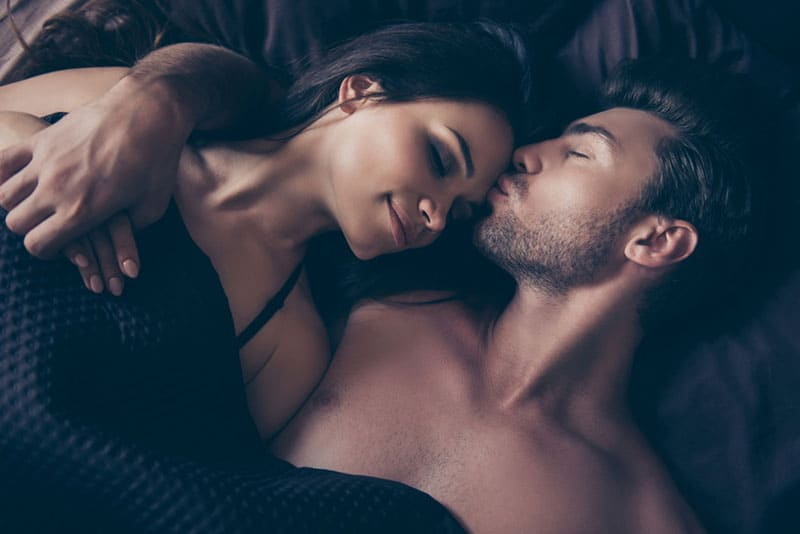 couple lying on bed man kisses woman forehead