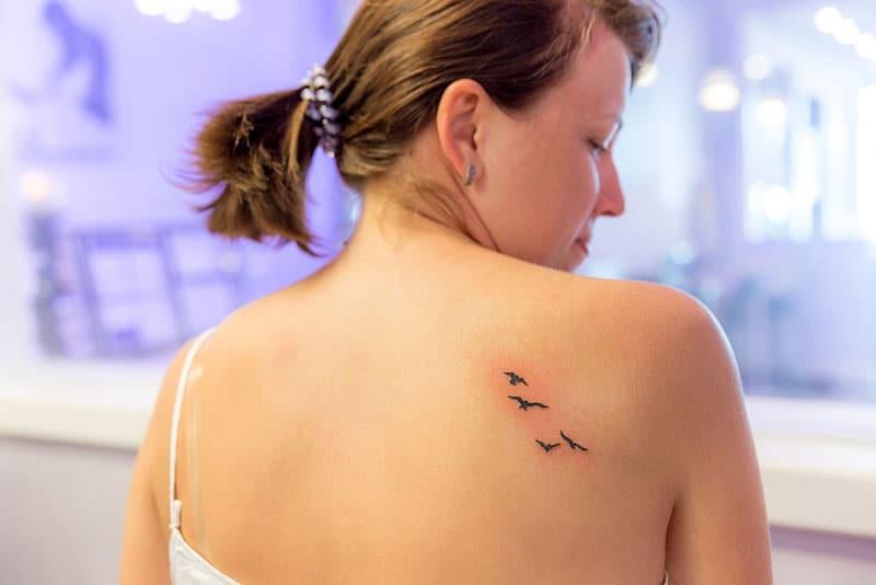 fresh tattoo of birds on womans shoulder