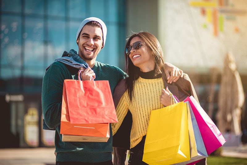 happy couple with shopping bags posing