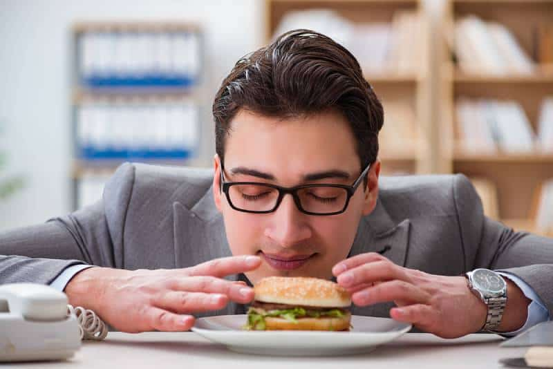 hungry businessman eating sandwich