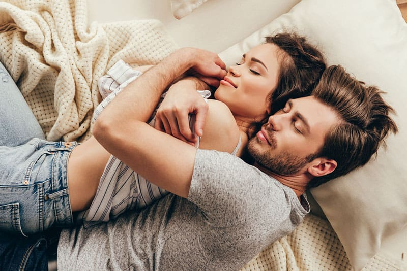 lovely couple lying on bed man hugs woman from back