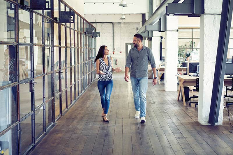 man and woman looking each other and walking in office