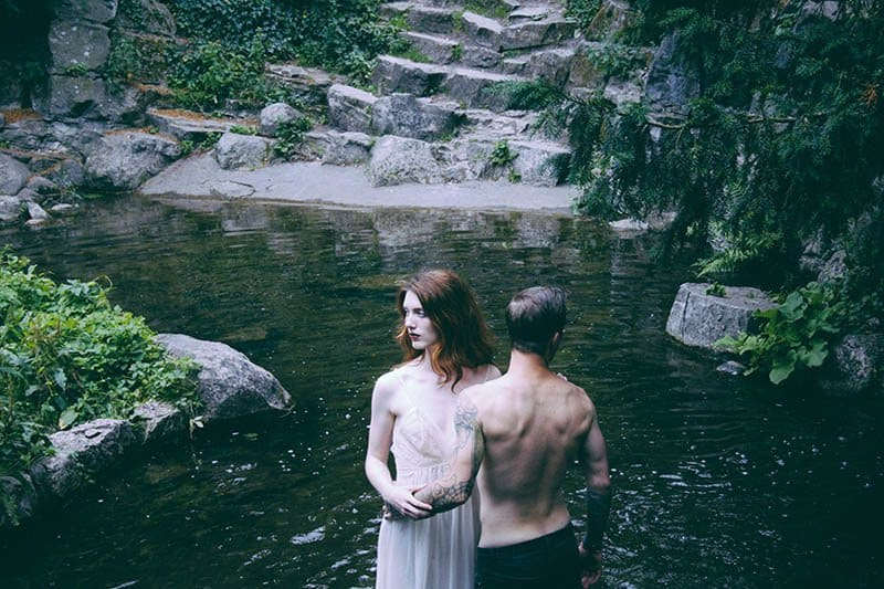 man and woman standing on rocks by the water