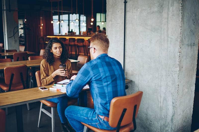 man and woman talking at cafe