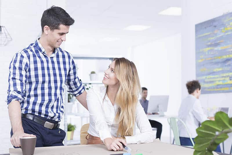 man and woman talking while man standing at office