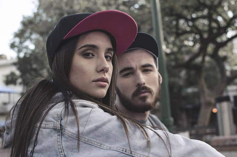 man and woman wearing hat and looking at camera outside
