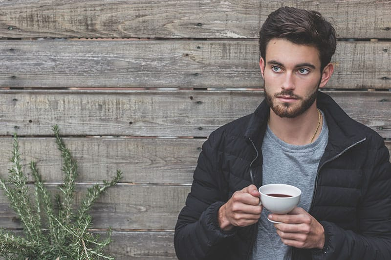 man holding a cup of coffee while leaning on wooden wall