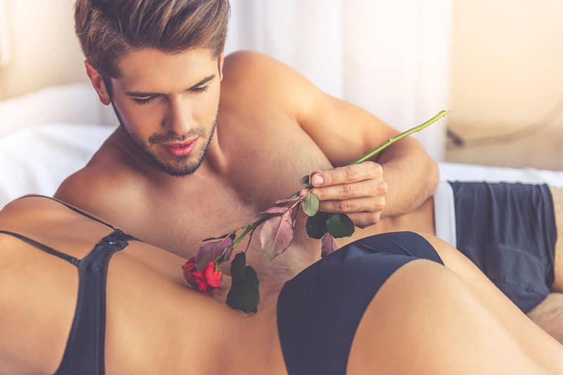 man holding a rose on womans back