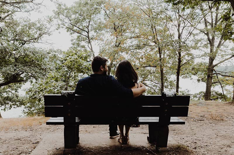 man hugs woman outside on a park bench