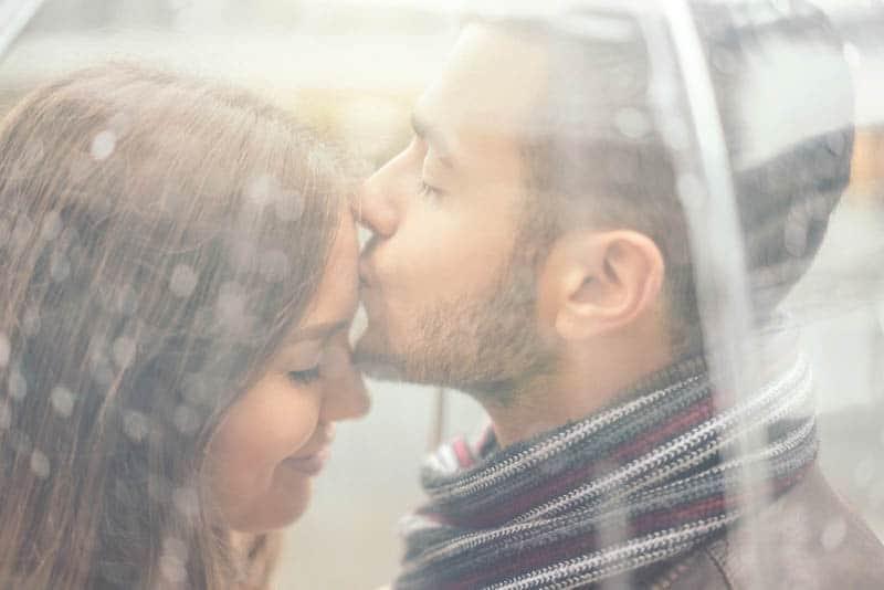 man kisses cute woman forehead