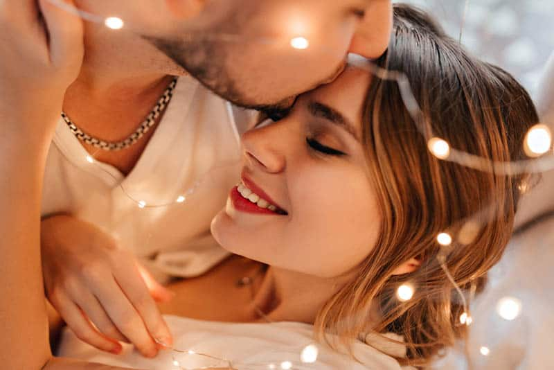 man kisses smiling woman in forehead