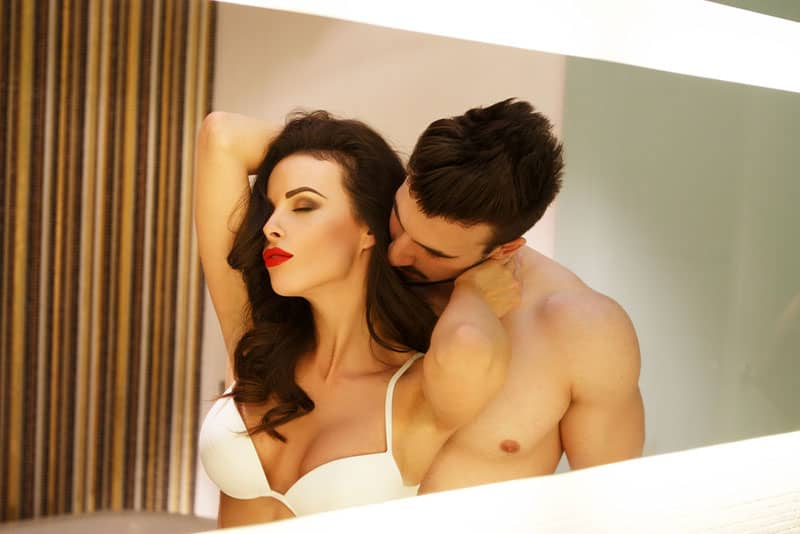 man kissing womans neck in front of mirror