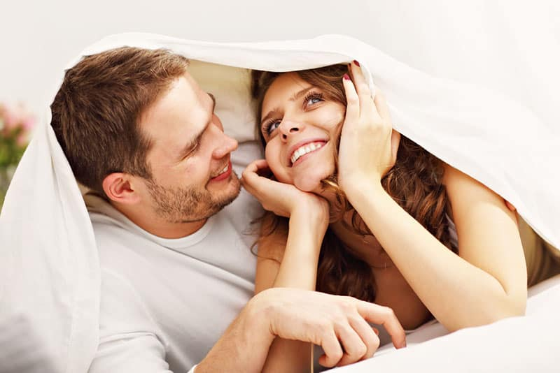 man looking at smiling woman under the blanket