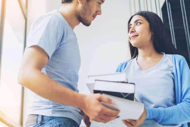 man picked up books to woman while looking at each other