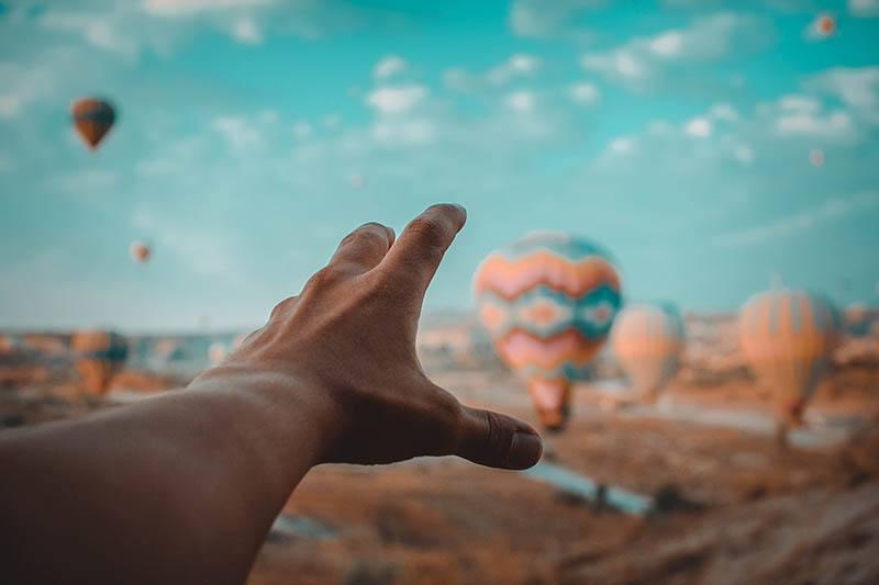 man raise hand to hot air balloons
