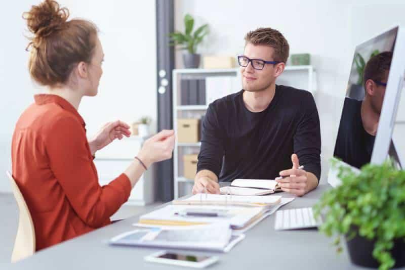 man talking to girl at office desk