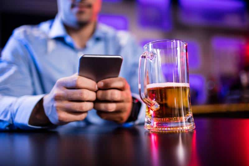 man typing on his phone with beer on table in bar