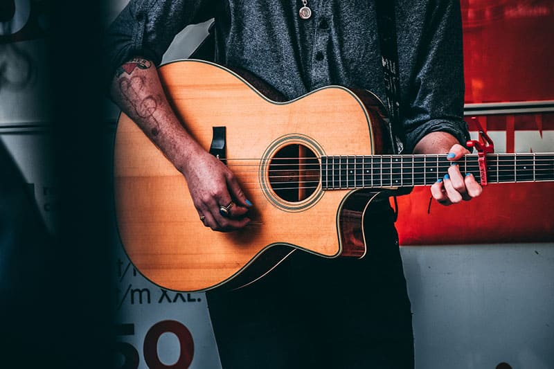 man with clef tattoo playing a guitar