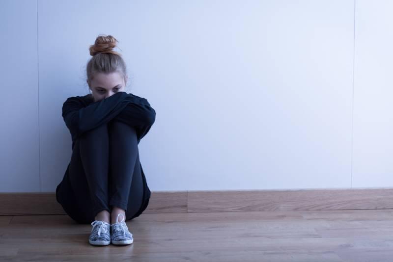 sad woman sitting on floor at home