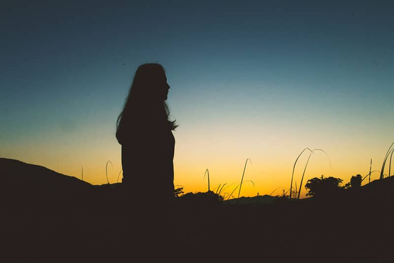side view silhouette of woman standing outside